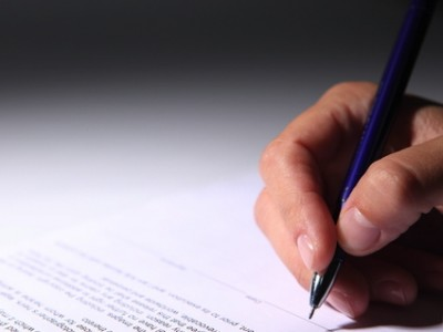 stock photo of a man's hand writing on a document